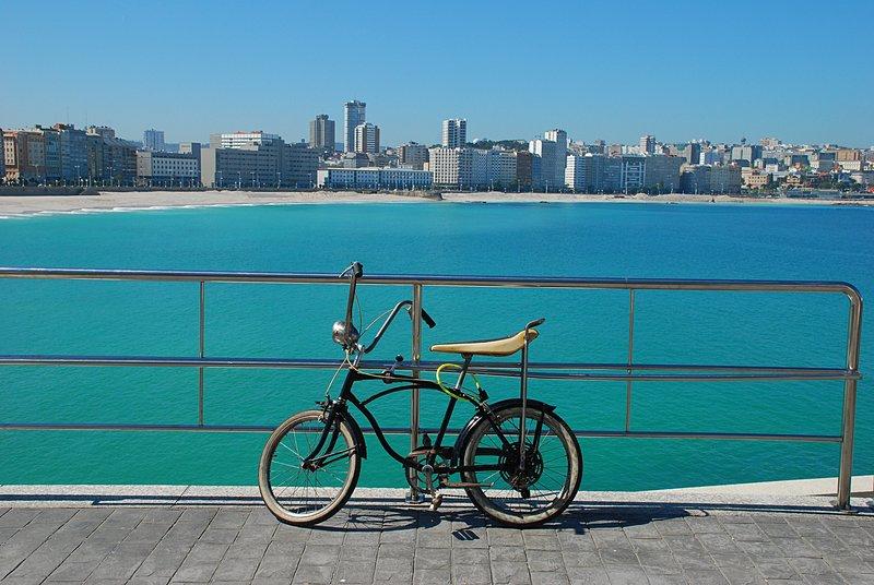 Bildet viser en sykkel med vakker sjø i bakgrunnen fra La Coruña i Galicia.